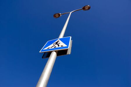Guide sign, column of illumination against the dark blue sky. photo
