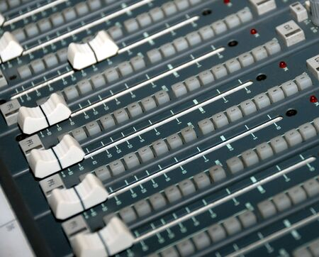 electronic balance: Audio mixing console in a recording studio. Faders and knobs of a sound mixer. Stock Photo