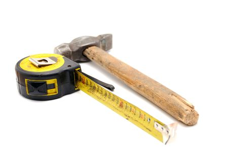 Old rusty tape measure and old hammer with wood handle on white background photo