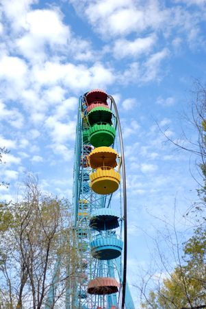 Ferris Wheel against trees and the sky with clouds photo
