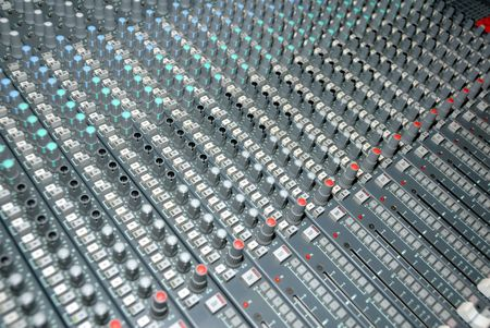 Audio mixing console in a recording studio. Faders and knobs of a sound mixer. photo