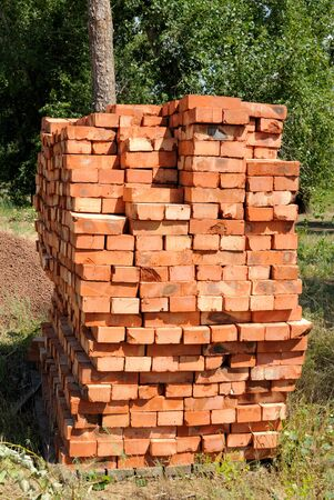 A pile of new red bricks at construction site sitting on wooden flat. photo