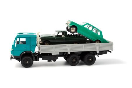 Toy cars in the back of toy truck on a white background photo