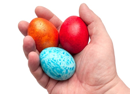 Coloured eggs for easter in hand on white background photo