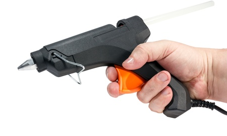 cohere: Electric hot glue gun in hand isolated on a white background. Stock Photo