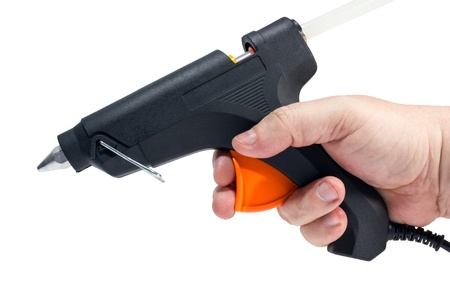 fastening objects: Electric hot glue gun in hand isolated on a white background. Stock Photo
