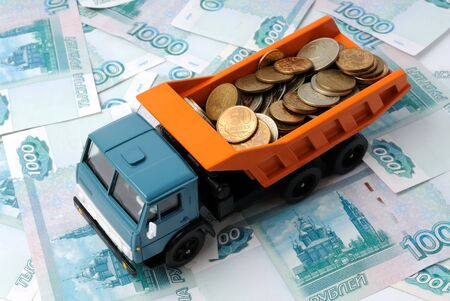Transportation of small coins for the toy truck. Concept. photo