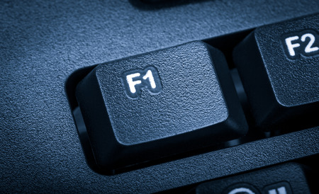 f1: Electronic collection - detail black computer keyboard. The focus on F1 key. Toning is blue.