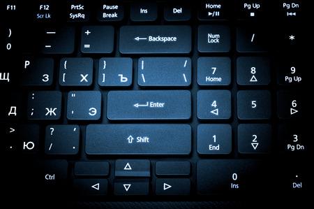 teclado de computadora: colección electrónica - teclado del ordenador portátil de cerca con la letra ruso. El enfoque en la tecla Intro. Tonificación es azul.