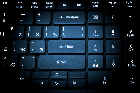 keyboard key: Electronic collection - close-up laptop keyboard with russian letter. The focus on the Enter key. Toning is blue. Stock Photo