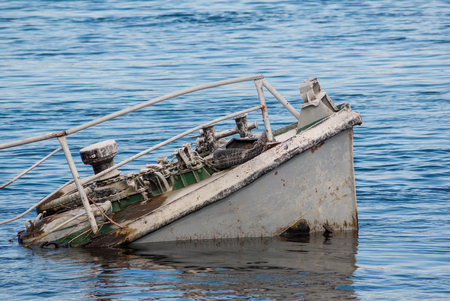 boat accident: Rusty ship wreck in a blue river Stock Photo
