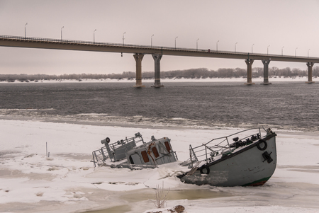 snow break: Vessel wreck in a frozen river covered with ice