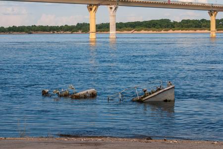 sunk: Rusty sinking vessel in a blue river