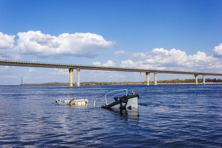 sunken: Rusty sunken vessel in a blue river Stock Photo