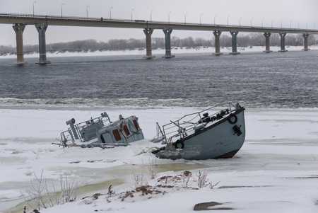 vessel sink: Sinking ship in a frozen river covered with ice Stock Photo