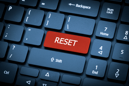 Close-up laptop keyboard. The focus on the Reset key. Toning is blue.