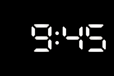 Real white led digital clock on a black background showing time 9:45