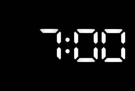 Real white led digital clock on a black background showing time 7:00