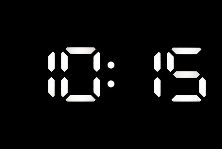 Real white led digital clock on a black background showing time 10:15