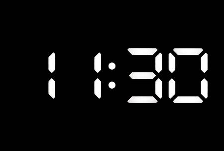 Real white led digital clock on a black background showing time 11:30