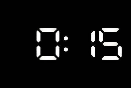 Real white led digital clock on a black background showing time 0:15