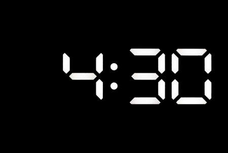 Real white led digital clock on a black background showing time 4:30