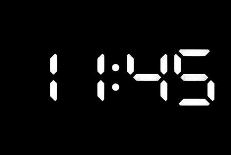 Real white led digital clock on a black background showing time 11:45