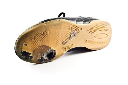 Worn out sports Shoe with hole on bottom, white background.