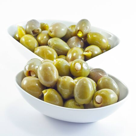 Green olives staffed with chili papers and almonds served as appetizer isolated on white background.