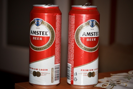 Two 0 5 liter cans of Amstel Premium Lager Beer sitting on the table