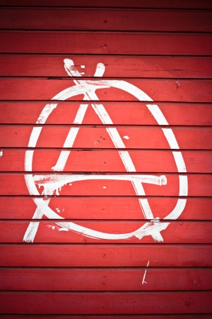 Anarchy sign painted on red wall in white color