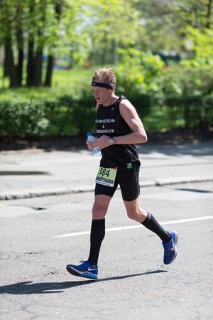 Belgrade, Serbia - April 21, 2018: Competitor dressed in black runs in the 31st Belgrade Marathon
