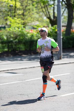 Belgrade, Serbia - April 21, 2018: Competitor with white cap and black sunglasses runs in the 31st Belgrade Marathon