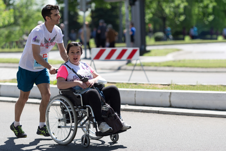 Belgrade, Serbia - April 21, 2018: Disabled woman in wheelchair, during 31st Belgrade marathon, is helped by runner. Editorial