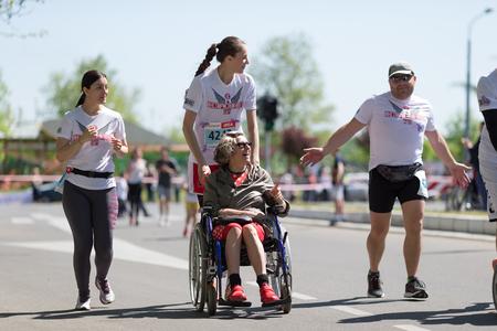 Belgrade, Serbia - April 21, 2018: Disabled woman in wheelchair, enjoying race during 31st Belgrade marathon, helped by runners.