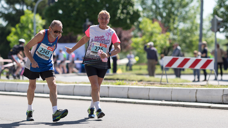 Belgrade, Serbia - April 21, 2018: An elderly man runner is cheered and encouraged by elderly woman competitor