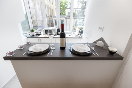 Red wine bottle served with plates, forks, spoons, knifes and glasses on modern kitchen bar in luxury apartment. Stock Photo