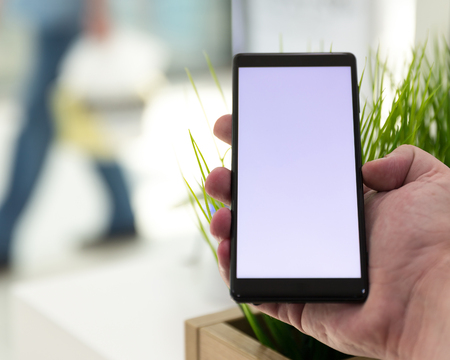 New mobile Smartphone with empty white screen shown in hand on blurry background. Digital gadget for internet and telecommunication