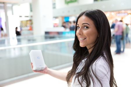 Belgrade, Serbia - Jun 23, 2018: New Honor 10 mobile Smartphone is shown in original box. Beautiful promo girl holding cellphone in hand on blurry background. Editorial