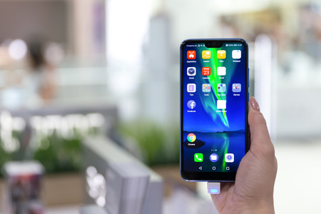 Belgrade, Serbia - Jun 23, 2018: New Honor 10 mobile Smartphone is shown with home screen in hand on blurry background