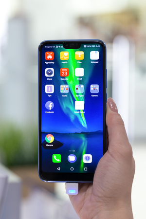 Belgrade, Serbia - Jun 23, 2018: New Honor 10 mobile Smartphone is shown with apps on the screen in hand on isolated background