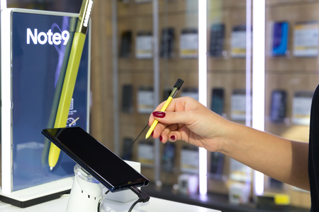 Belgrade, Serbia - August 14, 2018: New Samsung Galaxy Note 9 is displayed on brand logo stand in electronic store. Girl testing S pen in hand.
