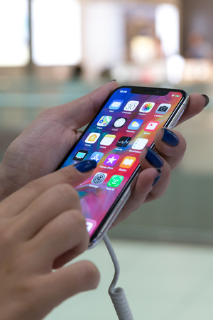 Belgrade, Serbia - August 30, 2018: New Apple iPhone X is shown in electronic store with apps on the screen in hand while typing with finger. Editorial