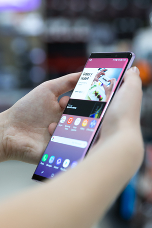 Belgrade, Serbia - August 30, 2018: Newly launched Samsung Galaxy Note 9 Smartphone is displayed with retail mode on the screen. Mobile phone in hands is shown in electronic store. Editorial