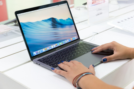 Belgrade, Serbia - August 30, 2018: New MacBook Pro laptop with macOS on the screen is shown on retail display in electronic store.