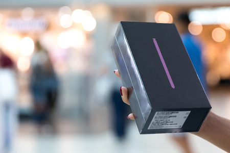 Belgrade, Serbia - August 30, 2018: New Smartphone, Samsung Galaxy Note 9 is displayed in original box, holded with a hand against isolated blurry background