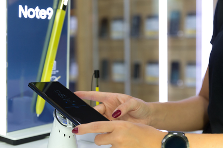 Belgrade, Serbia - August 14, 2018: New Samsung Galaxy Note 9 Smartphone is displayed on brand logo stand in electronic store. Girl testing mobile phone in hands. Time and date on the screen.
