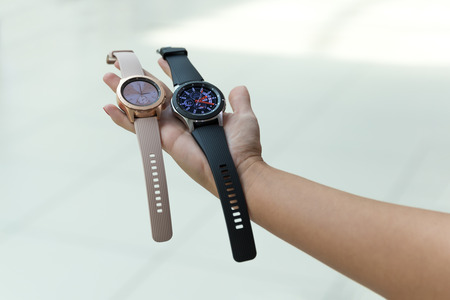 Belgrade, Serbia - September 13, 2018: New Samsung Galaxy Watch 46 mm - SM-R800 and 42 mm - SM-R810 are displayed in hand against isolated background. Two gadgets, silver one and gold rose, showing time on the screen.
