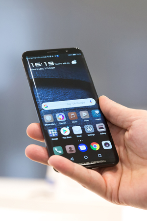 Belgrade, Serbia - October 03, 2018: Huawei Mate RS Porsche design is displayed with home screen on isolated background. Close-up of mobile smartphone with apps on the screen in hand.