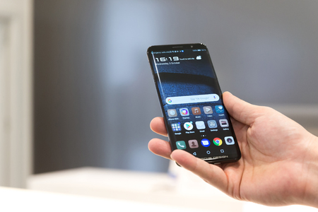 Belgrade, Serbia - October 03, 2018: Huawei Mate RS Porsche design is displayed with home screen in hand. Mobile smartphone with apps on the screen in electronic store.